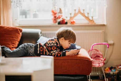 Kleiner Junge spielt am Sofa mit dem Smartphone