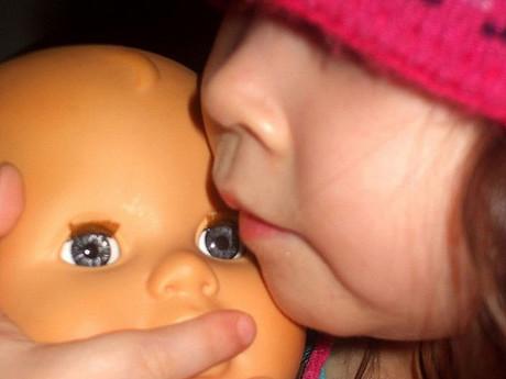 Mädchen mit Puppe im Arm.