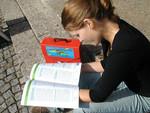 Ein Mädchen liest im Infomaterial der kija Salzburg.