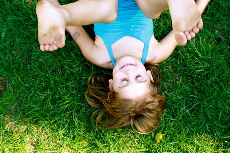 Ein Mädchen purzelt am Gras herum und lacht.