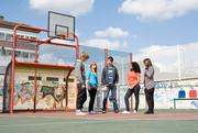 Gruppe von Jugendlichen auf einem Basketballplatz.