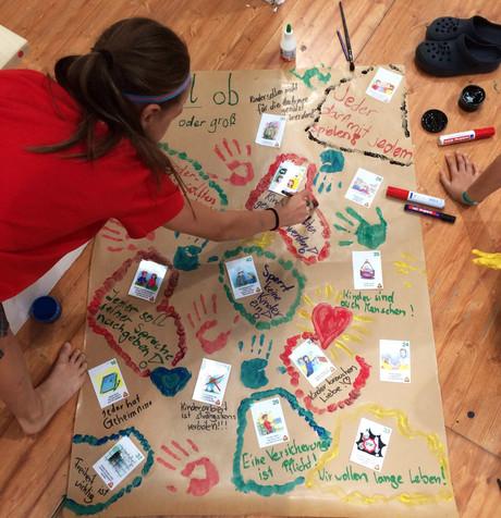 Mädchen malt ein Kinderrechte-Plakat.