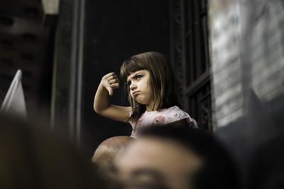 Bild eines Mädchens bei einer Demonstration, die den Daumen nach unten hält.