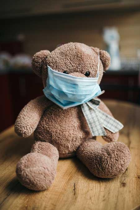 Teddybär mit Mund-Nasen-Schutz.